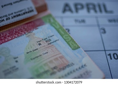 H1B visa (for specialty workers) stamp in passport, blurred april calendar on background. H1B visa program deadline concept. Close up view.