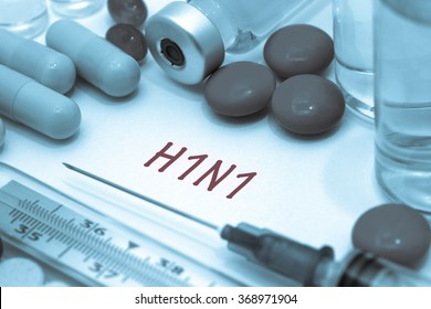 h1n1 - diagnosis written on a white piece of paper. Syringe and vaccine with drugs. Swine flu.