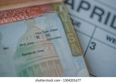 An H-4 visa (immediate family members of the H-1B visa holders) stamp in passport on blurred april calendar background.   H4 visa program deadline concept. Close up view.