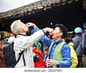 HA GIANG, VIET NAM - FEBRUARY 19, 2012: A tourist and a villager are together dringking. This action expresses friendly sentiments of native in North West in Vietnam.