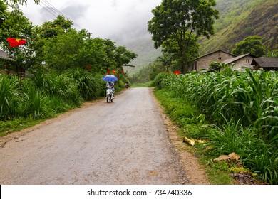 HA GIANG, VIETNAM - 5/24/2016: A villager motorbikes in the rain in Ha Giang, Vietnam