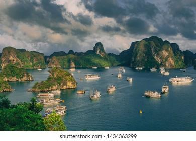 Ha Long Bay with boats around rocks island in the sea.