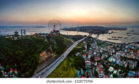 HA LONG, VIETNAM - SEP 28, 2018: Top view aerial photo from flying drone of a Ha Long City with development buildings, transportation, ferris wheel, aerial cable or telepheric.