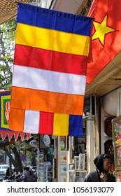 HA NOI, VIET NAM - 2018: A Buddhist flag in Hang Quat street.