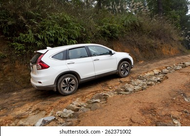 Ha Noi, Viet Nam - Dec 24, 2014: An SUV Honda model CRV 2015 crossing mud road in Vietnam