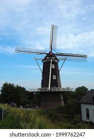 """Haaften, Netherlands - june, 27, 2021: Histoic windmill on the Waalbanddijk in Haaften, Netherlands. The flour mill """" de blauwe reiger"""" is build in 1856."""