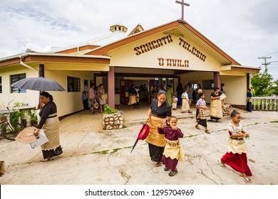 Haapai, Tonga - 5 Jan 2014: Polynesian parishioners in traditional Tongan dress walk out of church Sangata Teleisia 'o 'Avila as Catholic Mass ends, Pangai village, Ha'apai Group in Tonga, Polynesia.