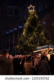 """Haarlem, Netherlands - 12.9.2018: Giant Christmas tree with lights and illuminated star towers over a crowd of happy people and """"hot chocolate"""" market stall at a holiday Christmas street market."""