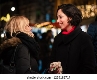 Haarlem, Netherlands - 12.9.2018: Happy young woman at a holiday Christmas street market, holding her debit or credit card while smiling at another woman. Two joyful people together outdoors.