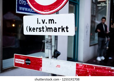 """Haarlem, Netherlands - 12.9.2018: A large red and white traffic stop sign blocks cars from accessing a road, saying """"in connection with (Christmas) market"""" during the yearly holiday street market."""