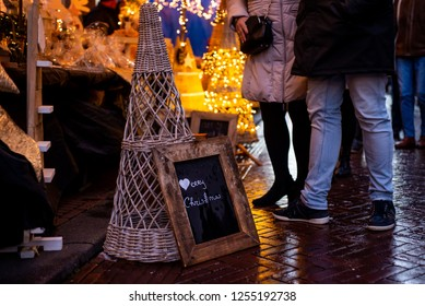 """Haarlem, Netherlands - 12.9.2018: """"Merry Christmas"""" written on a chalkboard sign with a wooden frame, at a holiday Christmas street market. Late in the evening, at dusk, with people on the street."""