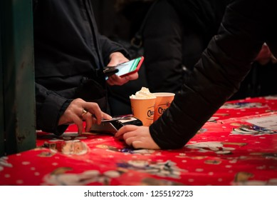 Haarlem, Netherlands - 12.9.2018: Person holding phone pays with a contact debit or credit card for two hot chocolates at a holiday Christmas street market. Bright red, festive tablecloth.