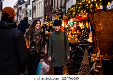Haarlem, Netherlands - 12.9.2018: Two happy young women walking in a Christmas street market, laughing and smiling and talking. One woman holds shopping bags. Background shows lights and vendor stalls