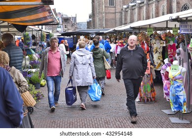 Haarlem, Netherlands - June 13, 2015: Outdoor market on the town square of Haarlem. Weekly market with various products. Market stall showing clothes and flowers.
