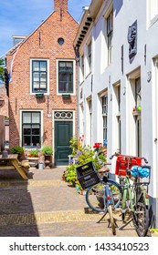 Haarlem, The Netherlands - May 31, 2019: Cozy green little street in the city center of Haarlem with a traditional Dutch gable house in the background