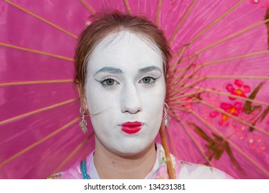 HAARZUILENS,THE NETHERLANDS - APRIL 17: Woman with white painted face and pink umbrella at the yearly Fantasy Fair event on April 17,2011 in Haarzuilens,Utrecht The Netherlands.