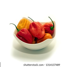 Habanero pepper in a white bowl on white background.