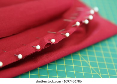 haberdashery. white pearl head pins in  material fabric before stitching together with sewing machine or hand sewn. red burgandy cloth on a green cutting mat. multiple needles on a hem. textiles class