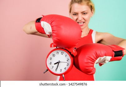 Habits and regime concept. Improve yourself. Overcome harmful habits. Time for training. Get used to personal regime. Girl athlete boxing gloves and alarm clock. Sport lifestyle and healthy regime.