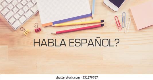 HABLA ESPANOL? Concept on Wooden Background