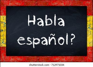 Habla espanol (translation: do you speak spanish) language education concept on chalkboard blackboard with wooden spain flag frame