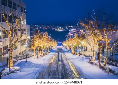 Hachiman Zaka Slope in Motomachi area with illumination light up with Hakodate bay in background. A famous and romance moment sloped street. Popular sightseeing spot in Hakodate City. Hokkaido, Japan