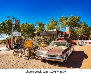 Hackberry, AZ, USA - July 12, 2016: Brown Chevy Antique Police Car and Antique Gas Pumps on Route 66 at Hackenberry General Store