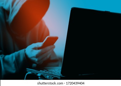 Hacker background. Black laptop and a sitting man in a hood without a face with a smartphone in hand backdrop.