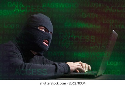 Hacker in a balaclava standing in the darkness furtively stealing data off a laptop computer on wooden background