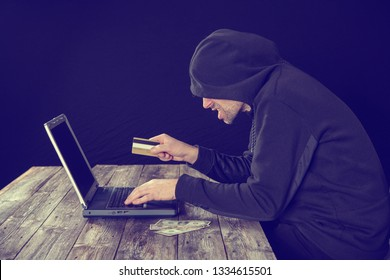 hacker in black hoody with laptop bank card and dollar notes in front of black background