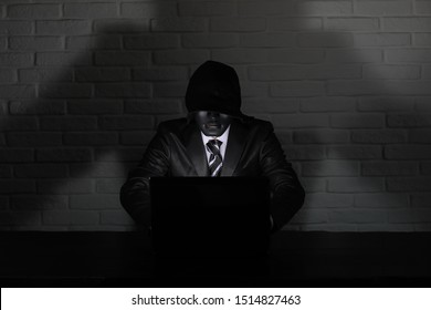 Hacker in black mask and hood at the table in front of the monitor