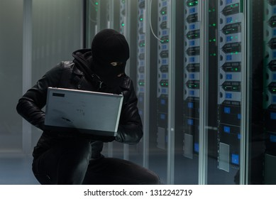Hacker in black mask using computer and breaking servers of data center stealing information