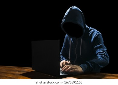 Hacker with computer man sitting at a table in a hood