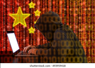 Hacker in a dark hoody sitting in front of a notebook with digital Chinese flag  background and binary streams cybersecurity concept