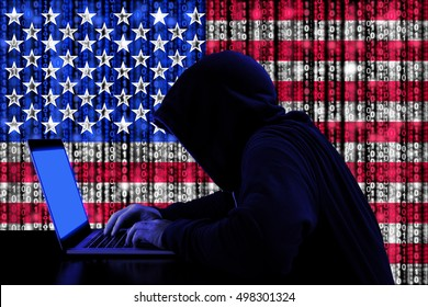 Hacker in a dark hoody sitting in front of a notebook with digital us flag and binary streams background cybersecurity concept