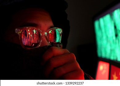 Hacker in a dark wearing hoody and cap sitting in front of computer with digital China flag background and binary code, cybersecurity concept.