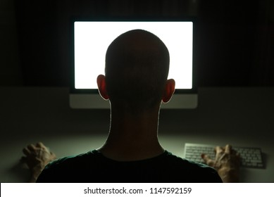Hacker doiing his crime on a desktop computer in the dark.