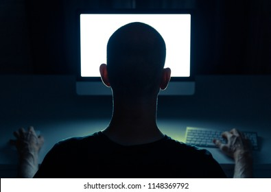 Hacker doing his crime on a desktop computer in the dark.