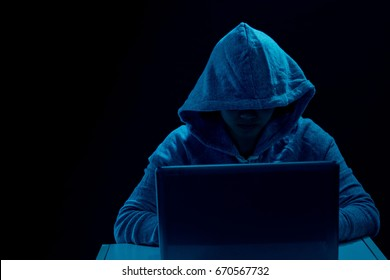 hacker in front computer with laptop / stealing information /Hacking the Internet/Dark face