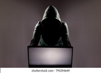Hacker in front of his computer. Dark face)