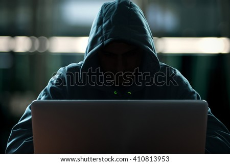 Hacker in front of his computer. Dark face