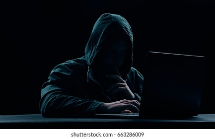 Hacker, hacker hacks network, hacker on a dark background