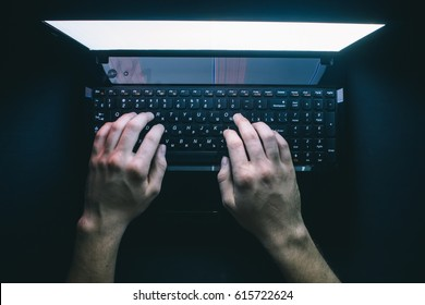The hacker hacks the server with bank accounts in a dark room on a black background in the dark.