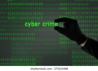 hacker hand in black glove holding cyber crime text in front of binary code computer screen in digital crime, hacking, cybercrime and illegal activity concept