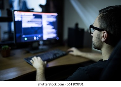 hacker in headset and eyeglasses with keyboard hacking computer system or programming