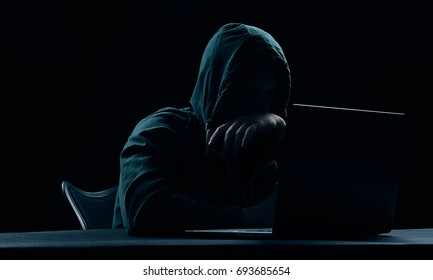 Hacker in a hood on a dark background