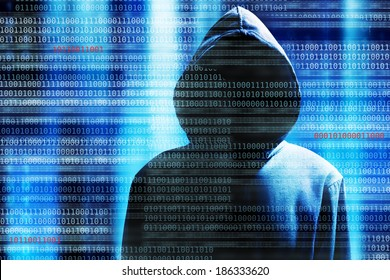 a hacker with a hood over a screen with binary code