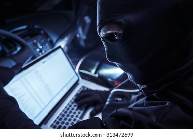 Hacker Inside the Car. Car Robber Hacking Vehicle From Inside Using His Laptop. Hacking On board Vehicle Computer.