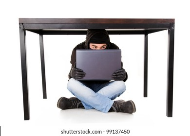 A hacker with laptop hidden under the office table, isolated on white