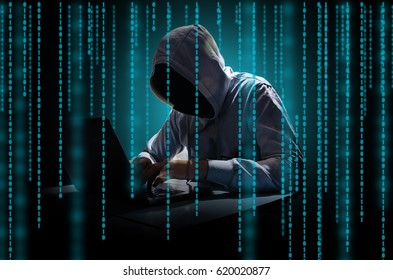 Hacker with a laptop on the screen binary matrix code. the concept of information security